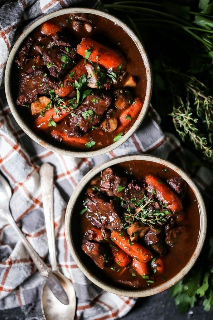 Overhead shot of two bowls of Beef Bourguignon filled with tender beef and carrots, placed on a plaid tablecloth with herbs in the background.