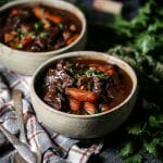 Two bowls of Beef Bourguignon filled with tender beef and carrots, placed on a plaid tablecloth with herbs in the background.
