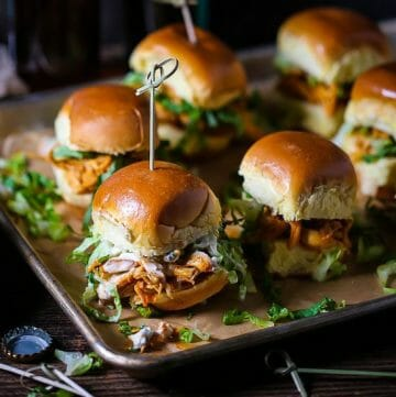 Buffalo Chicken Sliders skewered with knotted toothpicks on a sheet tray with beer in the background and a bottle cap on the table.