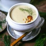 Roasted Fennel and Cauliflower Soup served in a footed white crock topped with roasted cauliflower and fennel fronds.