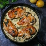 Chicken Breasts with Creamy Spinach Sauce cooked in a cast iron skillet.