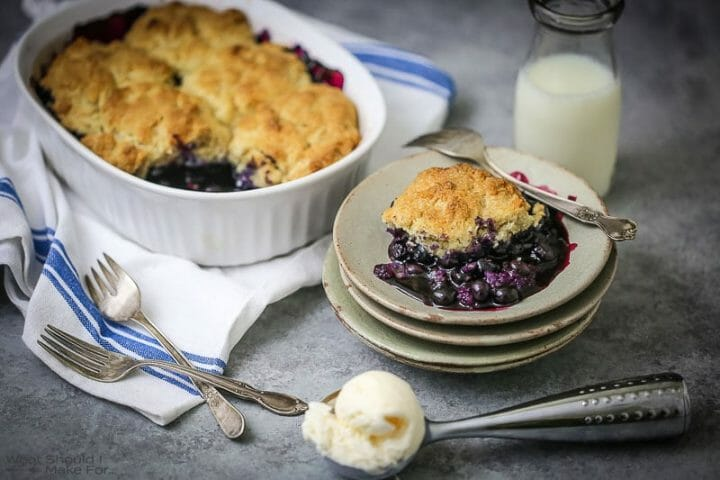 Blueberry Cobbler in the baking dish and on a small serving plate with ice cream scooped on the table.