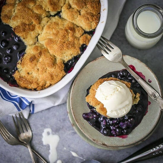 A serving of Blueberry Cobbler topped with vanilla ice cream next to the cobbler dish.