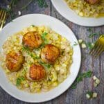 Close up shot of a serving of seared scallops over creamy fresh corn risotto.