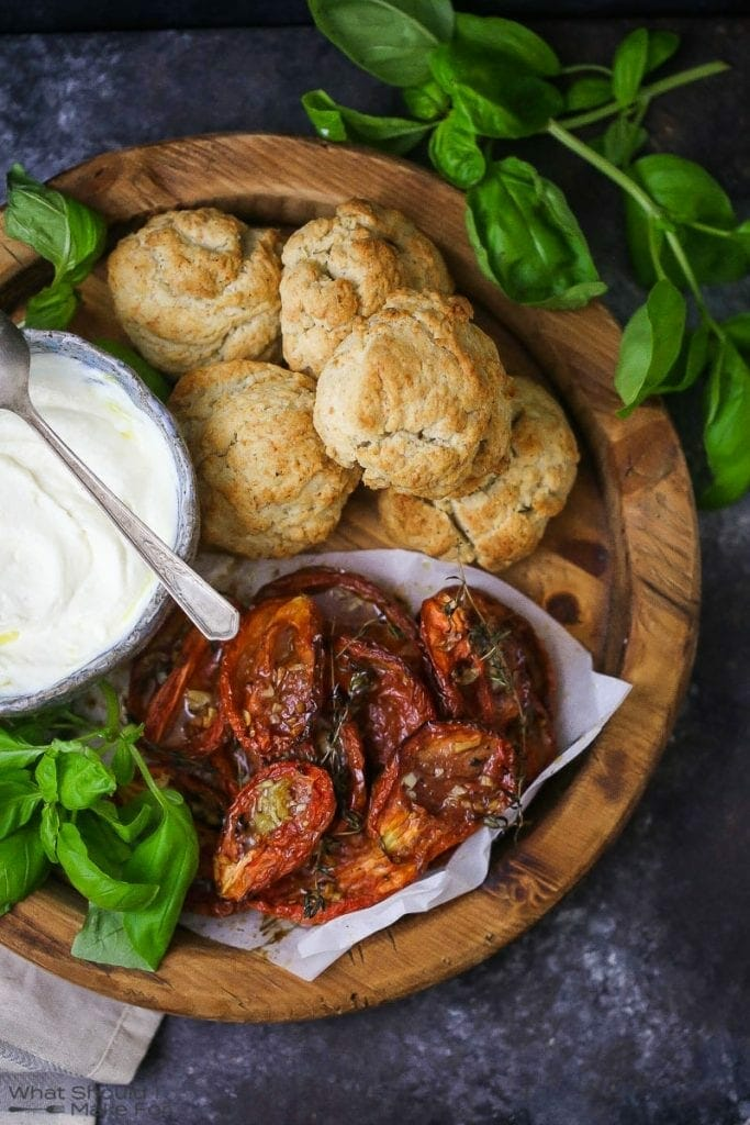 """Tomato """"Shortcake"""" with Whipped Ricotta ingredients on a round wood board with basil scattered around."""