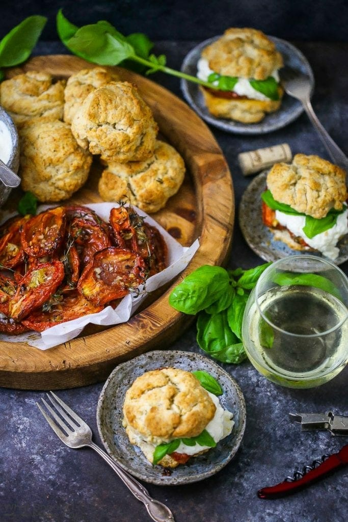 """Tomato """"Shortcake"""" with Whipped Ricotta ingredients on a round wood board with basil scattered around and assembled shortcakes and wine on the table."""