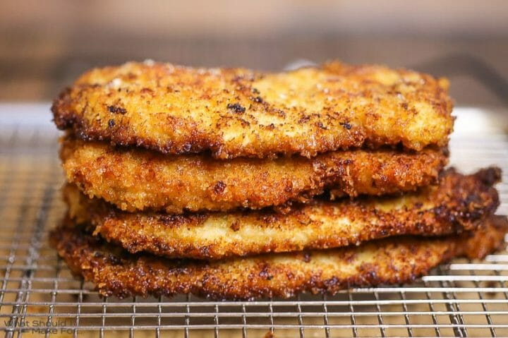 Close up of breaded chicken breasts stacked and cooling on a wire rack.