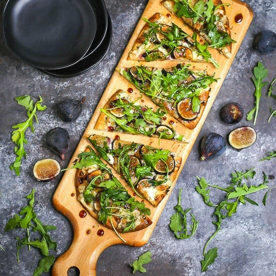 Fig, blue cheese, and arugula flatbread sliced and served on a wooden cutting board.