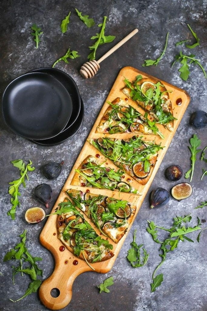 Fig, blue cheese, and arugula flatbread sliced and served on a wooden cutting board and drizzled with honey balsamic vinaigrette.