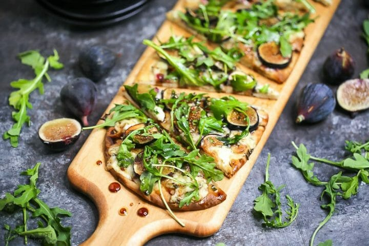 Close up of fig, blue cheese, and arugula flatbread sliced and served on a wooden cutting board and drizzled with honey balsamic vinaigrette.
