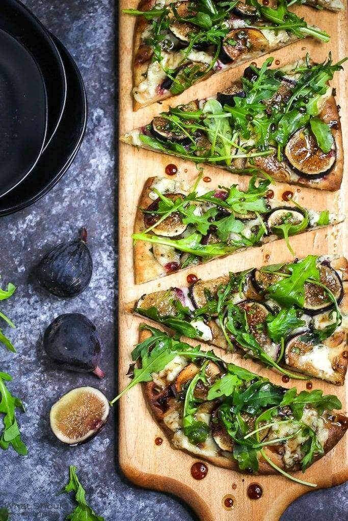 Close up of fig, blue cheese, and arugula flatbread sliced and served on a wooden cutting board.