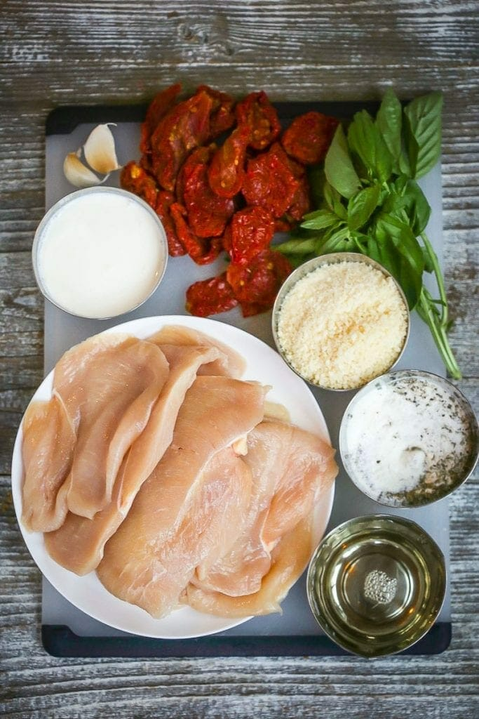 Gather ingredients for chicken with creamy sun-dried tomato sauce including thick cut chicken breasts, garlic, sun-dried tomatoes, basil, parmesan cheese, wine and seasonings.