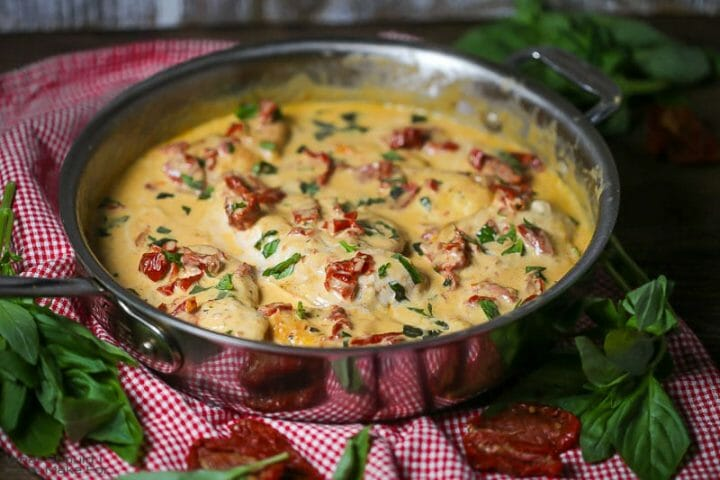 Close up of chicken with creamy sun-dried tomato sauce simmering in a saute pan sprinkled with fresh basil.