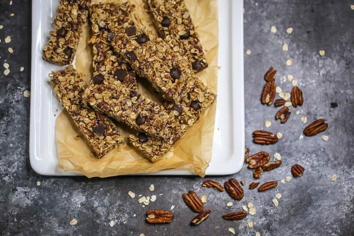 Homemade chocolate coconut pecan granola bars on plate with pecans scattered around.