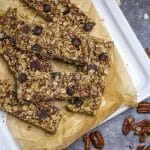 Close up of homemade chocolate coconut pecan granola bars on plate with pecans scattered around.