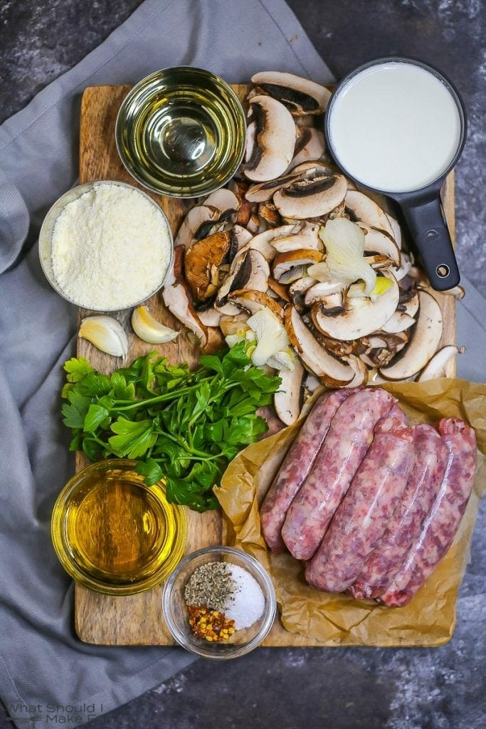 The ingredients for creamy pasta with mushrooms and sausage are gathered on a cutting board including wild mushrooms, sausage, parsley, olive oil, cream, and parmesan cheese.