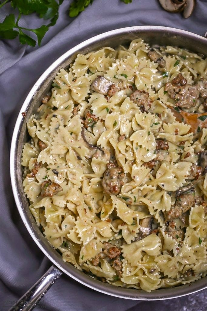 Close up of creamy farfalle pasta tossed with mushrooms and sausage in a creamy white wine sauce, in a large saute pan with a wooden spoon.