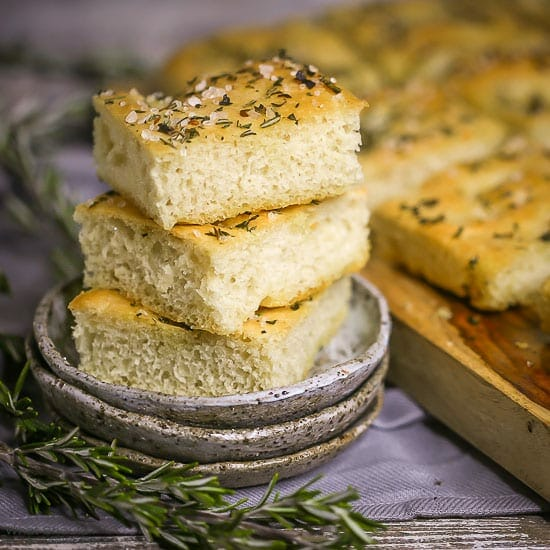 Three squares of Fluffy Focaccia Bread stacked on a little grey late with a couple sprigs of rosemary alongside.