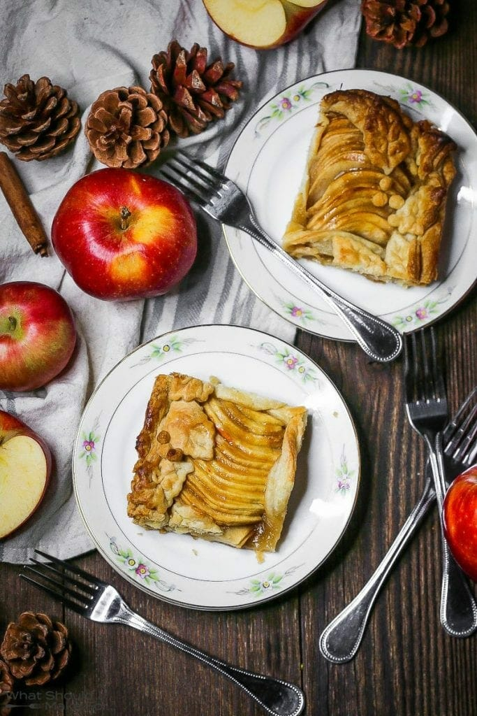 Square slices of Caramel Apple Slab Pie on plate with red apples and pinecones scattered around.