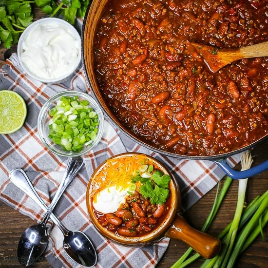 Overhead shot of Chili con Carne in a pot with a serving of chili alongside topped with sour cream, cheese, cilantro, and scallions.
