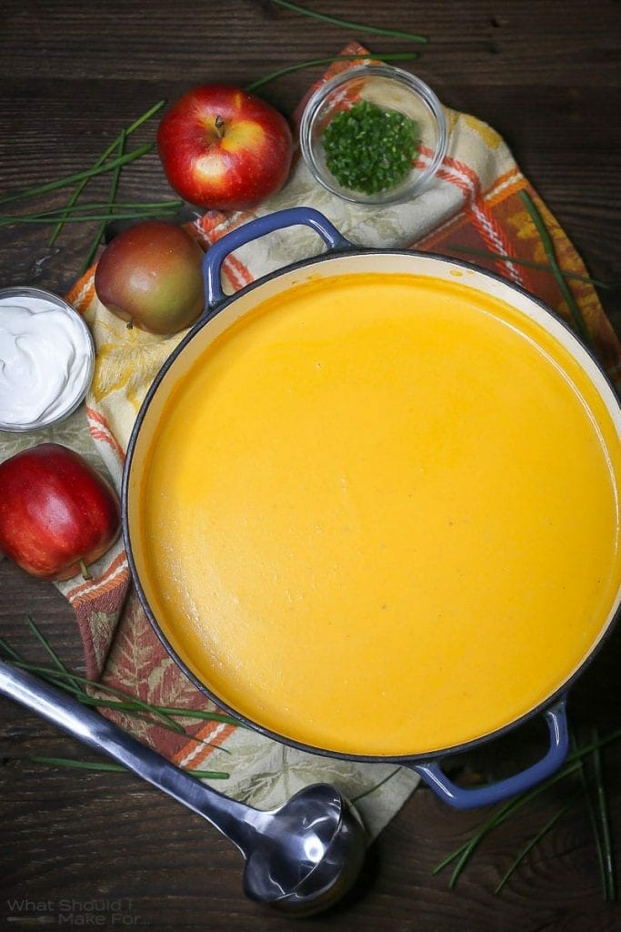 Overhead shot of Roasted Butternut Squash and Apple Soup in a pot with spoons, apples, and garnishes scattered around.