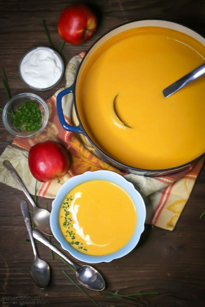 Overhead shot of Roasted Butternut Squash and Apple Soup in a blue bowl garnished with creme fraiche and chives, with spoons, an apple, and garnishes scattered around.