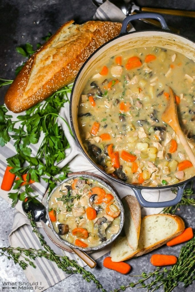 A serving of turkey stew in a bowl with a spoon, slices of bread, the pot, and herbs alongside.