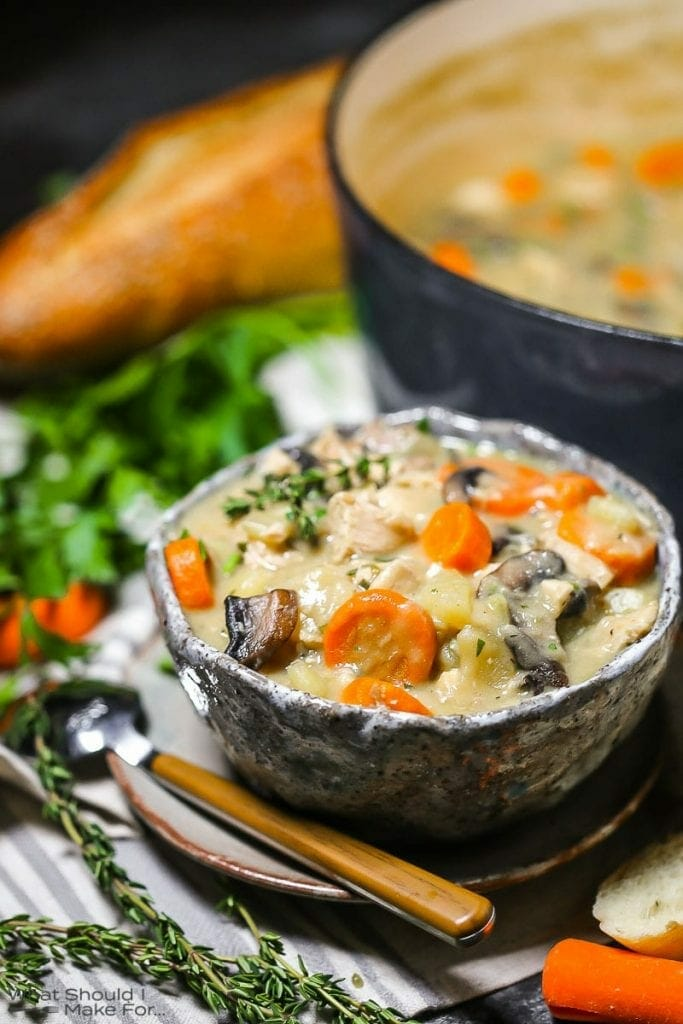 A serving of turkey stew in a bowl with a spoon, slices of bread, and herbs alongside.