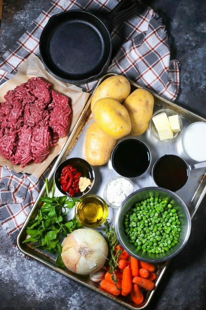 All the ingredients gathered to make Shepherd's Pie including potatoes, ground meat and vegetables.