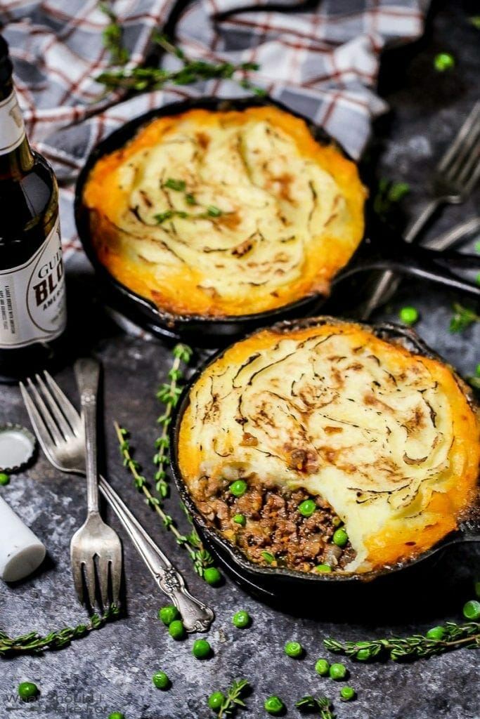 A shot of two individual servings of Shepherd's Pie in cast iron skillets with a few bites eaten, a golden crispy edged potato topping with thyme, peas, forks, and an open bottle of beer scattered around.