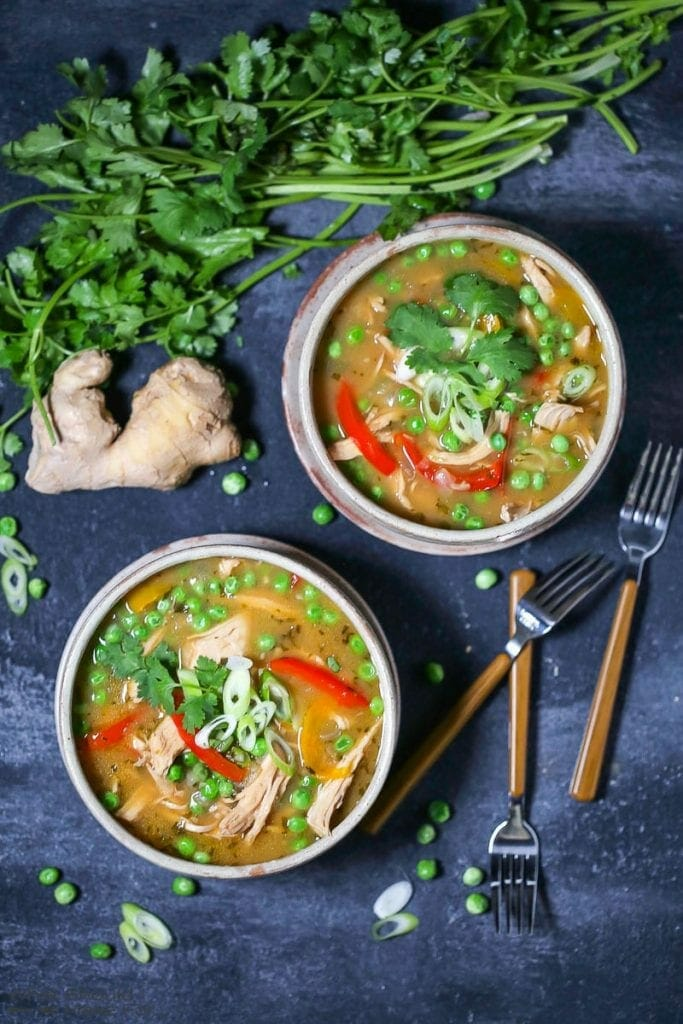 Two servings of Thai-Style Coconut Chicken Curry garnished with scallions, in a round bowl on a plate, with peas, ginger root, cilantro, and forks scattered on the table.