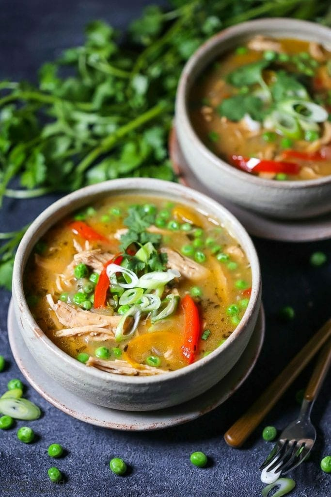 Two servings of Thai-Style Coconut Chicken Curry garnished with scallions, in a round bowl on a plate, with peas and cilantro scattered on the table.