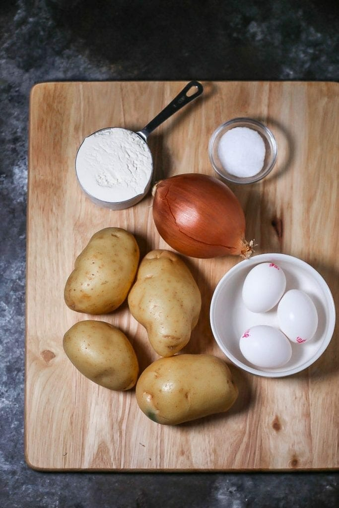 Ingredients for mini potato latkes including potatoes, onion, flour, salt and eggs.