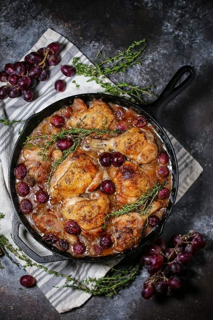 Braised Chicken with Grapes in a cast iron skillet with sprigs of thyme and grapes scattered around.