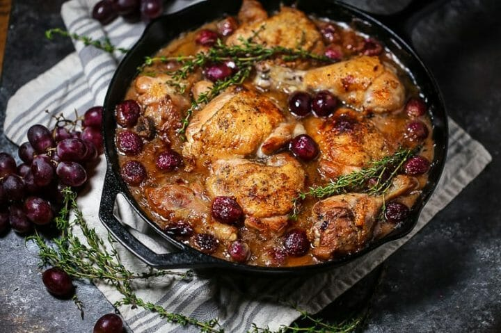 Braised Chicken with Grapes in a cast iron skillet with sprigs of thyme scattered around.