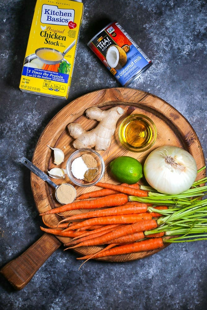Ingredients gathered for carrot ginger soup including carrots, ginger, onion, garlic, spices, stock and coconut milk.