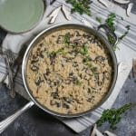 Overhead shot of creamy mushroom risotto in a silver saute pan with sprigs of thyme and mushrooms slices scattered around.