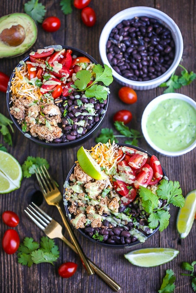 Chicken Burrito Bowls with Avocado Dressing drizzled over the top, garnished with lime and cilantro. Two gold forks are alongside the bowl and bean, avocado dressing, grape tomato, lime wedges and cilantro are scattered around.