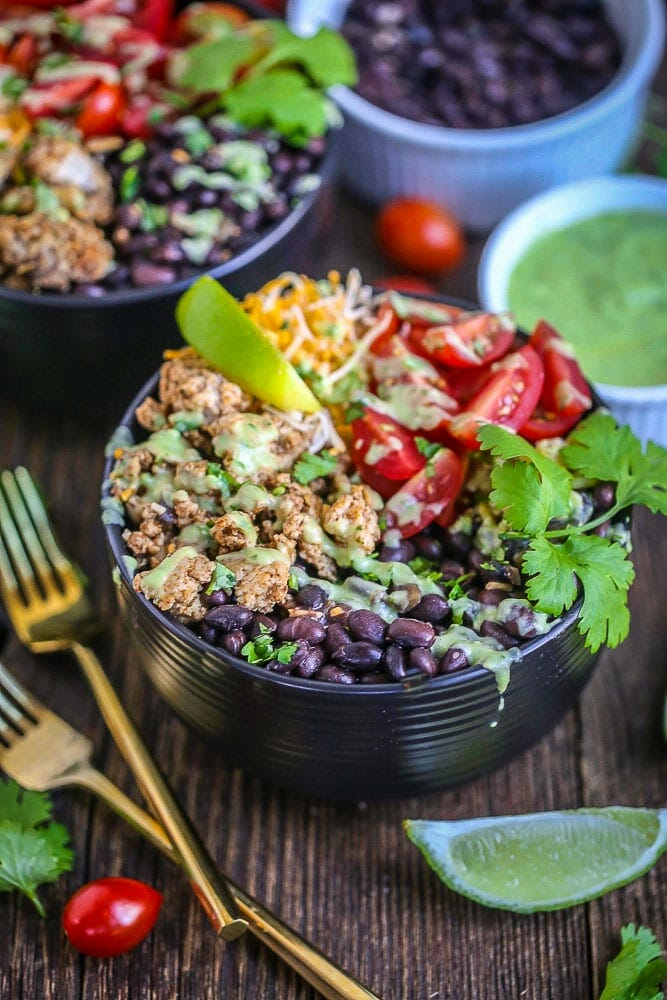 Chicken Burrito Bowl with Avocado Dressing drizzled over the top, garnished with lime and cilantro with two gold forks alongside.