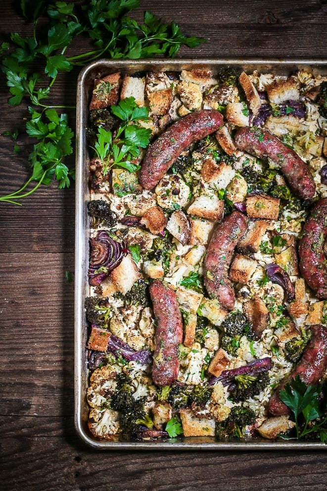 Overhead shot of Sausage Sheet Pan Dinner with Cauliflower and Broccoli on a dark wood table with fresh parsley sprigs in the corner.