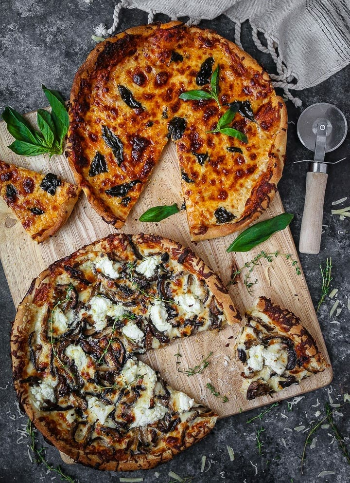 White mushroom and classic skillet pizzas on a cutting board with slices cut out, scatter with herbs and a pizza cutter laying on the table.