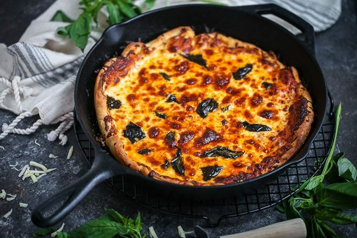Classic cast iron skillet pizza baked up and ready to be sliced with a pizza cutter and fresh basil scattered around.
