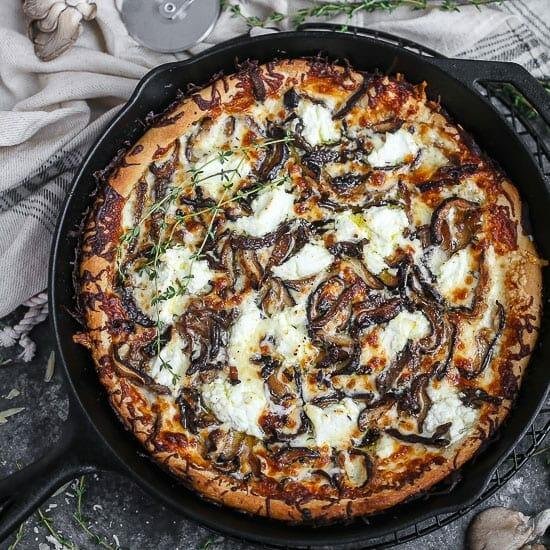 White mushroom pizza baked in a cast iron skillet, dolloped with ricotta and scattered with thyme sprigs.