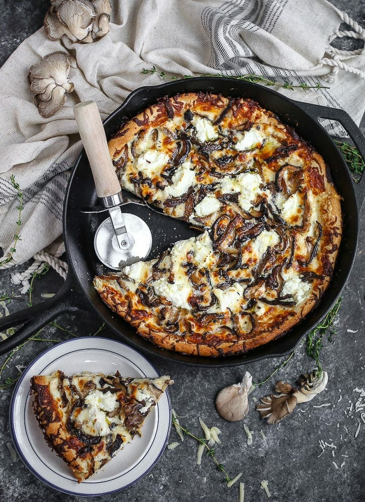 White mushroom pizza served in a cast iron skillet with a slice cut out and served on a small plate.