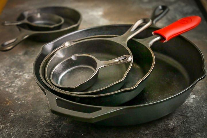 A stack of different size cast iron skillets, one with a red handle protector.