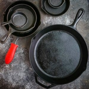 Different size cast iron skillets arranged on a table, one with a red handle protector.