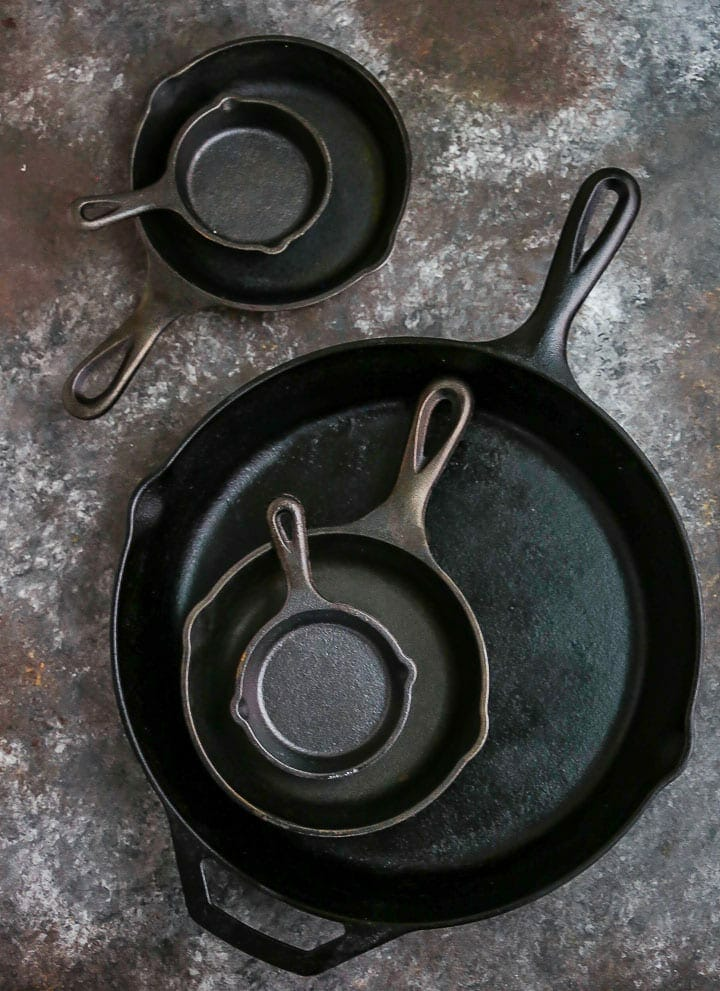 Different size cast iron skillets arranged on a table.