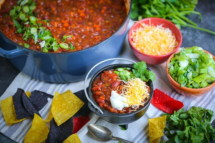 Hearty Vegetarian Chili is in a large pot sprinkled with herbs and a serving of chili is in a small bowl with cheese, chips and cilantro scattered around.