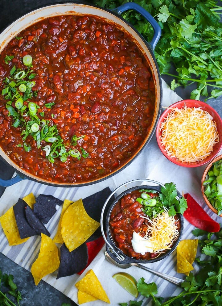 Overhead shot of Hearty Vegetarian Chili. The chili is in a large pot sprinkled with herbs and a serving of chili is in a small bowl with cheese, chips and cilantro scattered around.