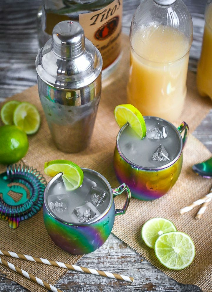 Overhead shot of Moscow Mules served in rainbow mugs with lime slices with a cocktail shaker, striped straws, ginger beer, and vodka scattered around.